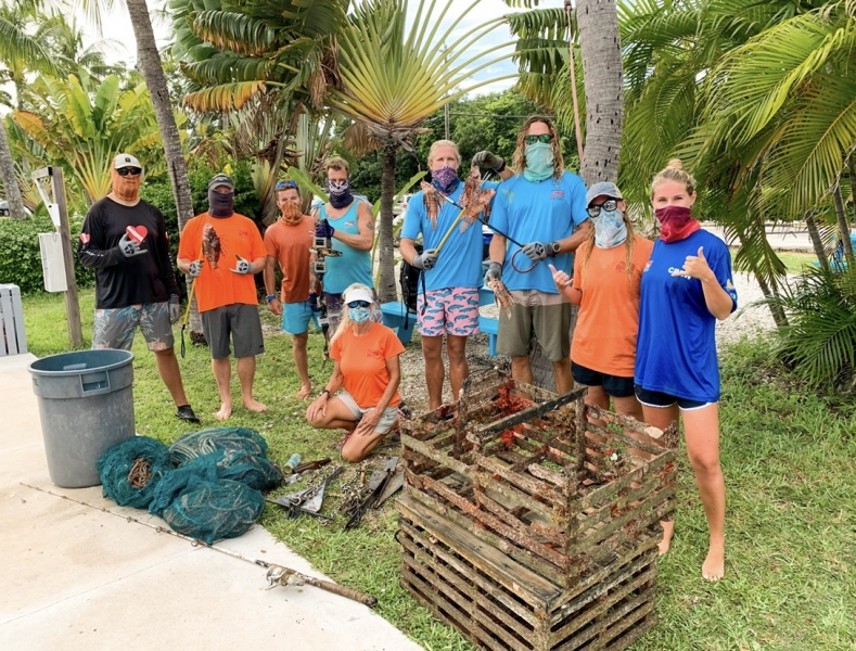 A group of divers posing with marine debris.