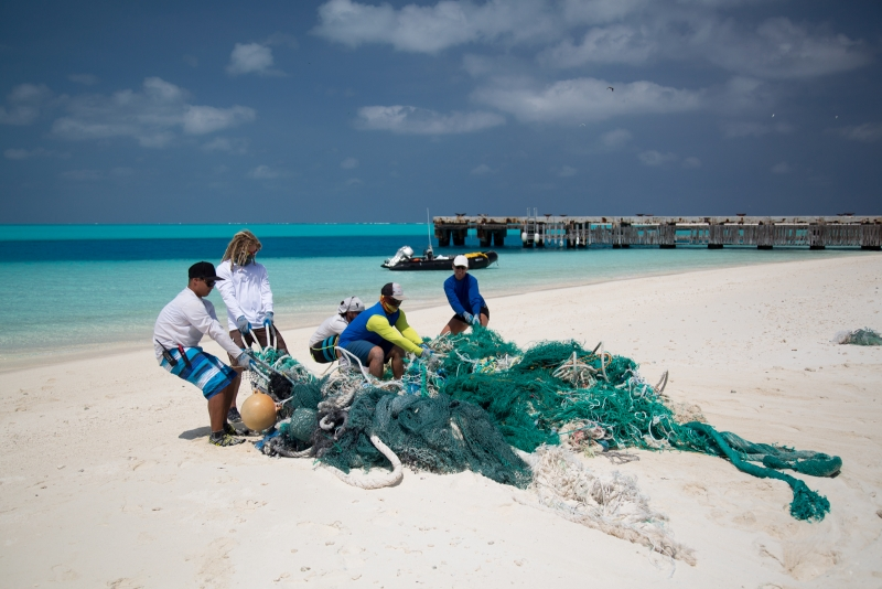 The Marine Debris team removing a large net conglomerate from the shorelines of Eastern Island, Midway Atoll.