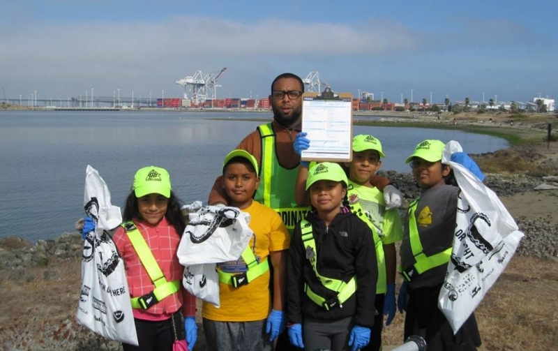 Kids and a chaperone on a beach with reflective gear and bags of debris and a city in the background.