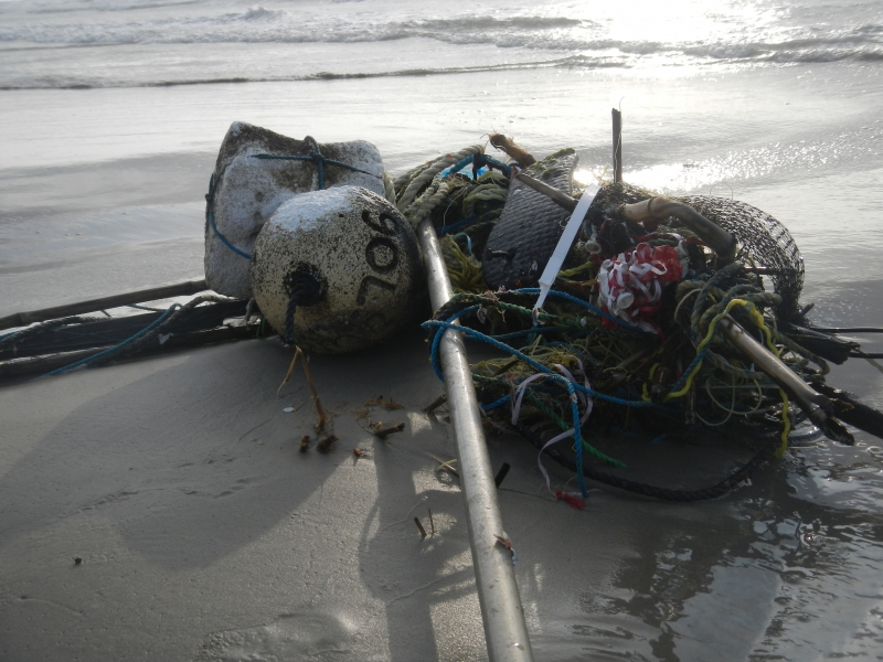 Marine debris, including a metal pole, buoy, and rope, lay tangled on a beach.