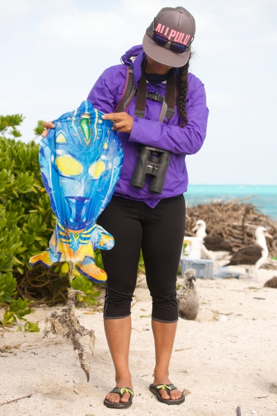 Researcher holding balloon debris and entangled Albatross.