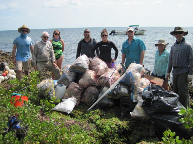 Eight people stand behind piles of garbage all stuffed in plastic garbage bags. A boat is floating on the water in the background.
