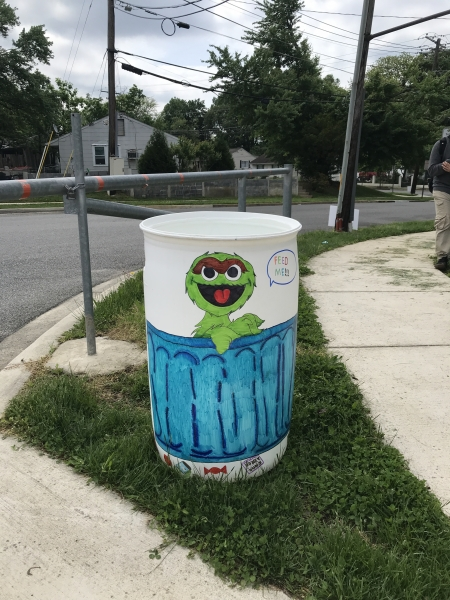 A white, plastic garbage can with a green Oscar the Grouch painted on the side.