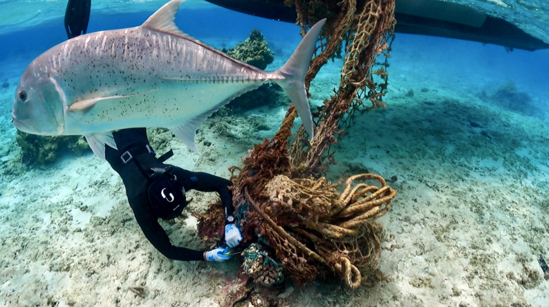 A marine debris removal team member cuts a large net from a reef at Hōlanikū