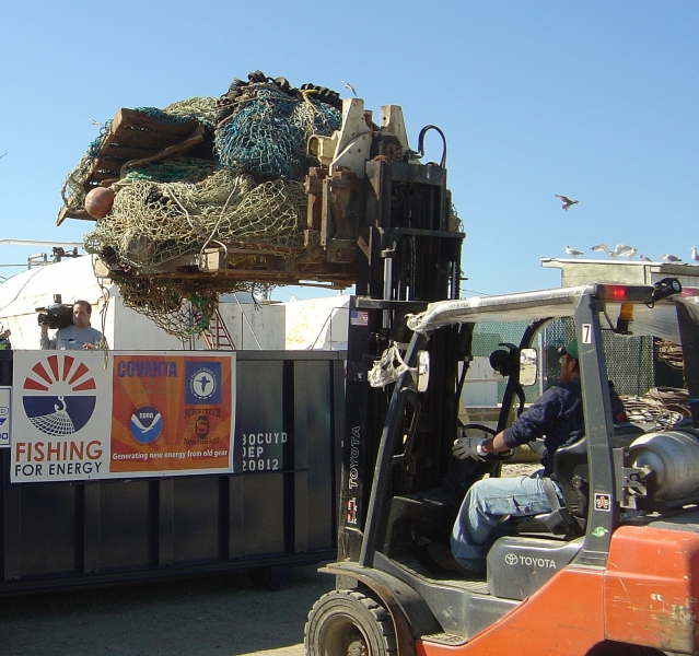A person uses a forklift to life a large pile of fishing gear into a dumpster.