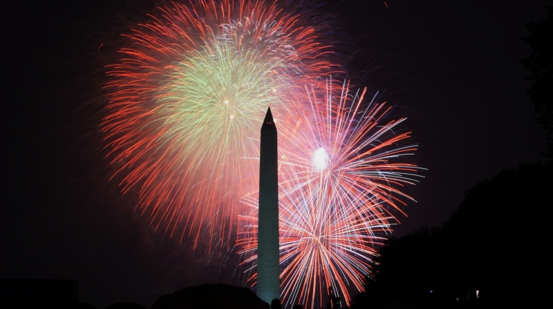 Fireworks light up the night sky behind the Washington Monument.