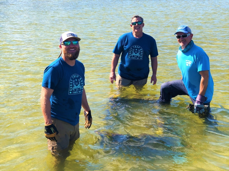 Three men smiling in knee deep water.