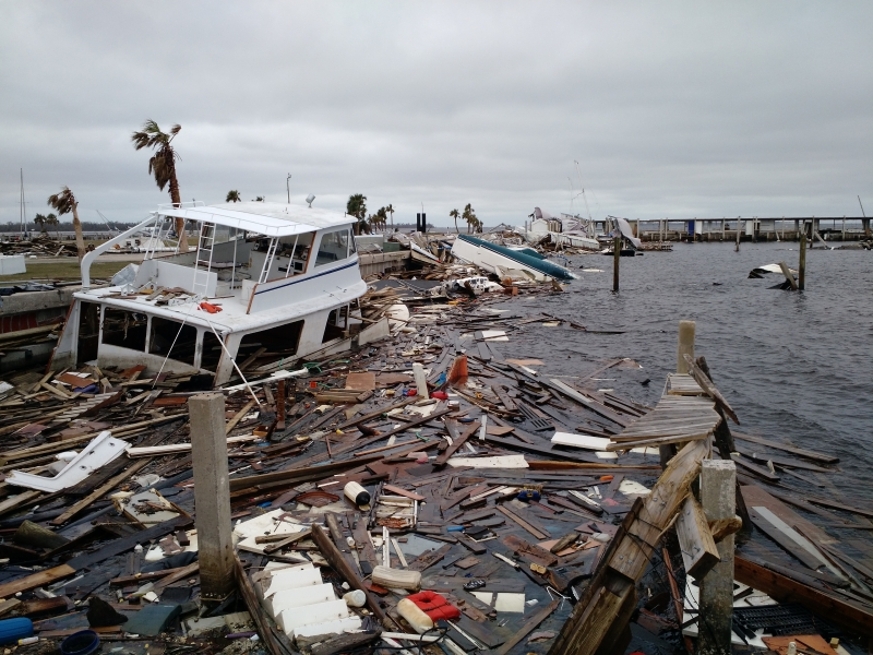 A half sunken boat is surrounded by floating wood debris caused by Hurricane Michael.