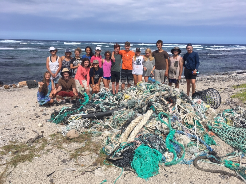 Beach cleanup volunteers with collected derelict nets.
