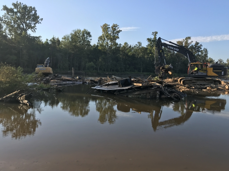 heavy machinery on the shore of a river.