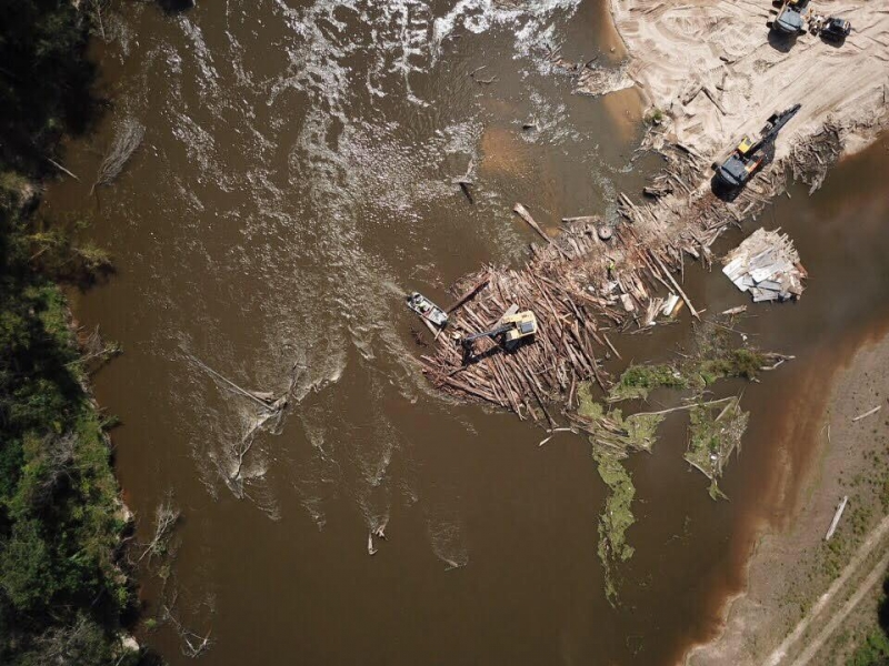 Several large construction excavators remove logs from a muddy river.