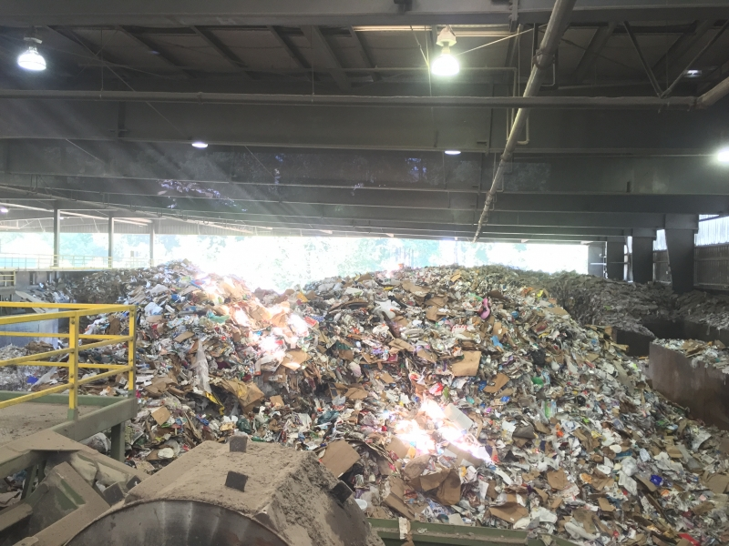 A large heap of trash at a recycling center.