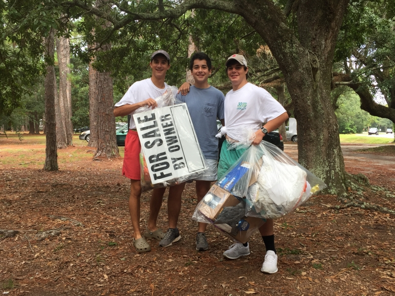 Three young men holding up trash