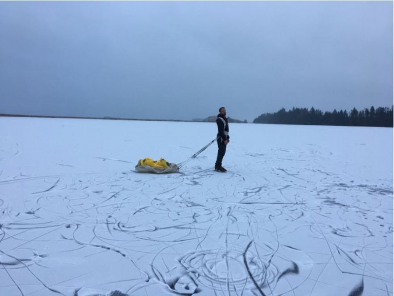 A person stands on a gently snow-covered frozen body of water pulling a small, yellow sled.