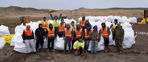 Seventeen people stand in a line for a picture with several white garbage bags full of marine debris.
