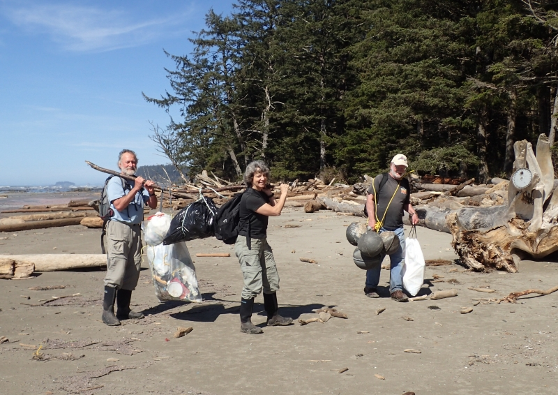 Three people carry several garbage bags filled with marine debris.
