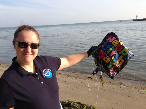 "A person holding balloon debris that says ""Happy Birthday!""."