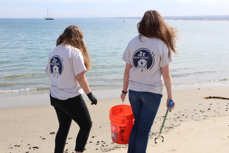 Girls collecting trash on the beach.