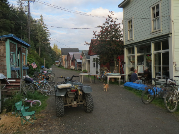 A trail runs between houses with an all terrain vehicle and several bikes.
