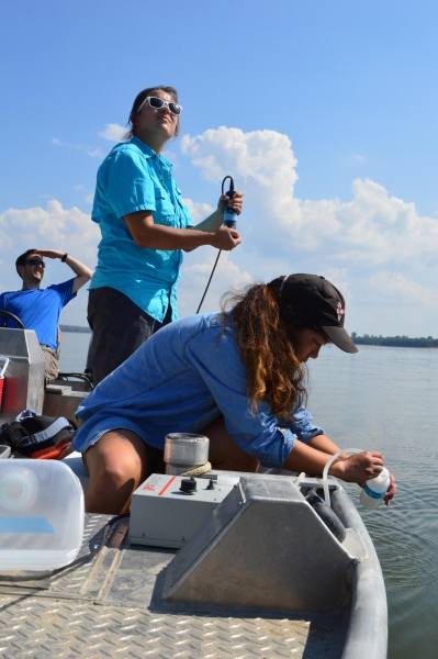 Two women and a man collect data on a boat.