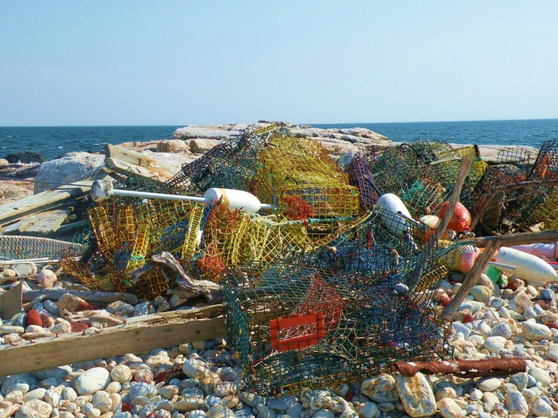 A pile of collected crab traps on a beach.