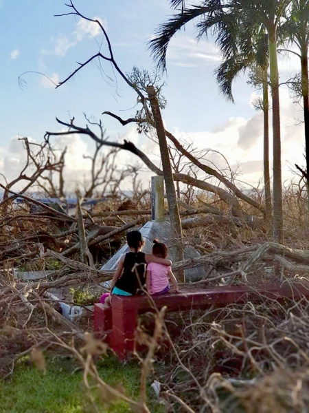 Two sisters observe the aftermath of Typhoon Yutu in the Mariana Islands.