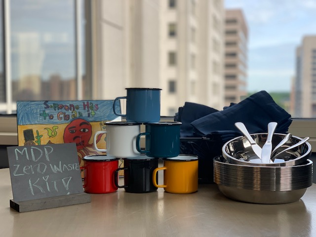 A zero waste kit containing reusable plates, utensils, cups, and napkins.