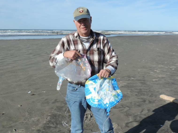 Russ Lewis with two balloons he found on the Washington coast.