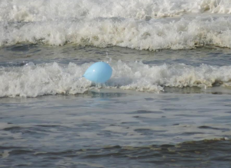 A rubber balloon coming ashore on the surf.