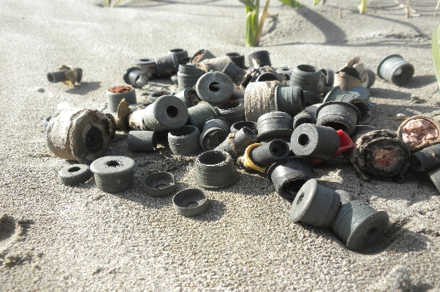 A pile of plastic plugs on a beach.