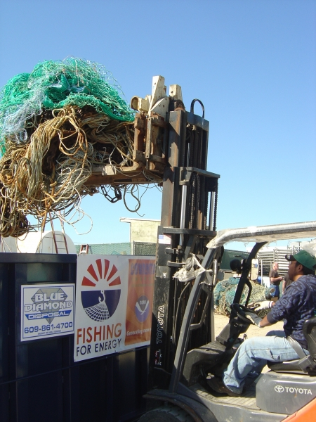 A man loads old fishing gear into a large metal bin by using a pallet jack.