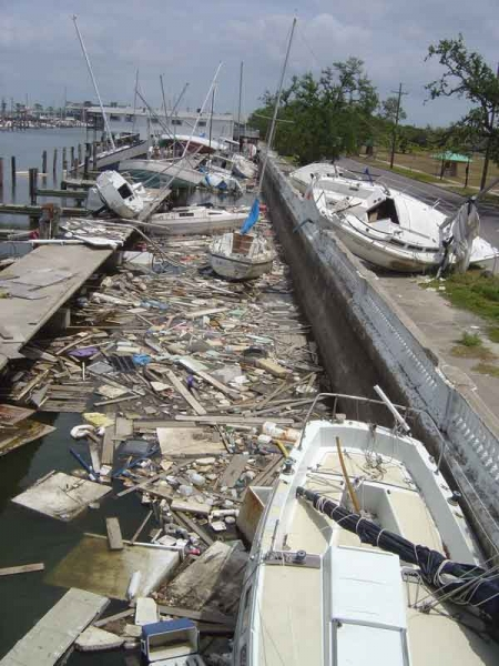 A marine with damaged boats and debris in the water.
