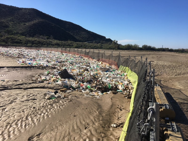 A fence and large weighted boom hold back plastic water bottles and other debris in the Goat Canyon Basin.