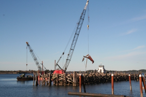 Boat debris being hauled out of the water with a crane.