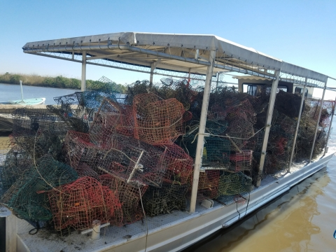 A boat that is full of collected, discarded crab traps that have been removed from the water.