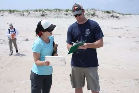 Two people on a beach, recording debris information on a clipboard.