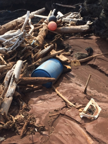 A barrel, buoys, and natural debris on a beach.