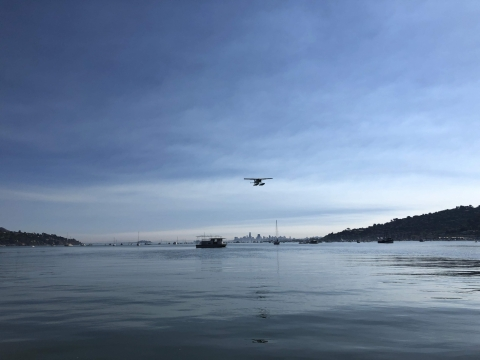 A seaplane begins to land on a smooth body of water.