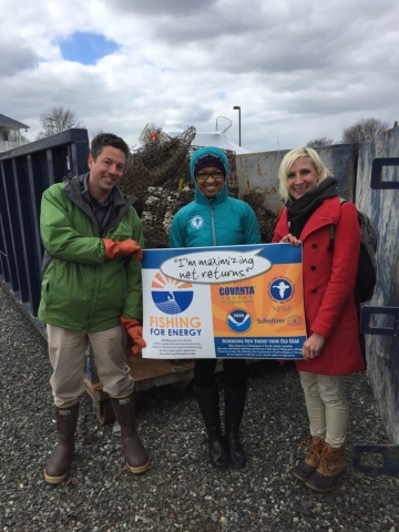 Three people at the event hold a Fishing for Energy sign in front of one of the collection bins.
