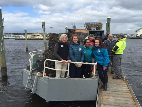Four event attendees stand on a boat loaded with derelict crab pots.