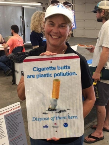 "A person smiles while holding a sign that says ""Cigarette butts are plastic pollution""."