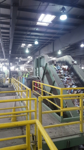 A conveyor belt with recyclable items at a recycling center, with workers in the background.