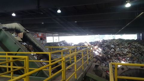 A large heap of trash and conveyor belt at a recycling center.