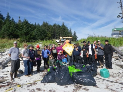A group of people posing with bags of collected debris.