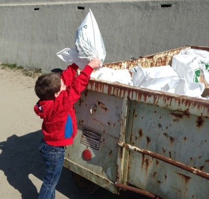 A child putting a bag of trash in a dumpster.
