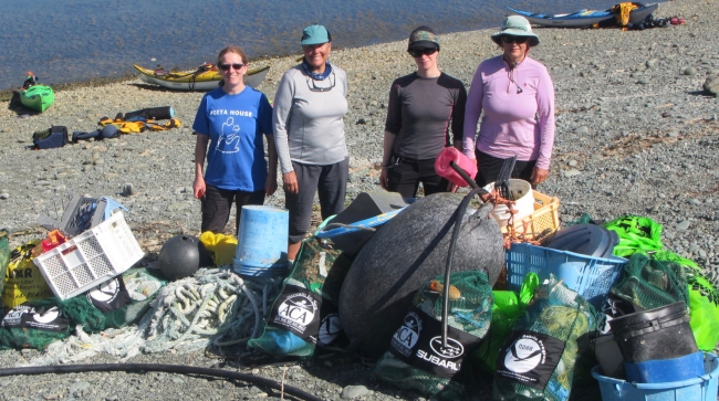 Four people standing on a beach in front of a pile of debris.