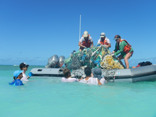 People in the water and on a boat, hauling large derelict nets onto the boat.