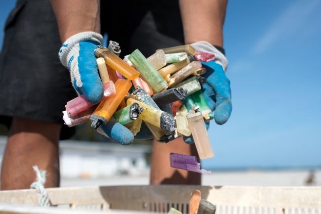A marine debris team member empties a handful of lighters collected from the shorelines of Midway Atoll.