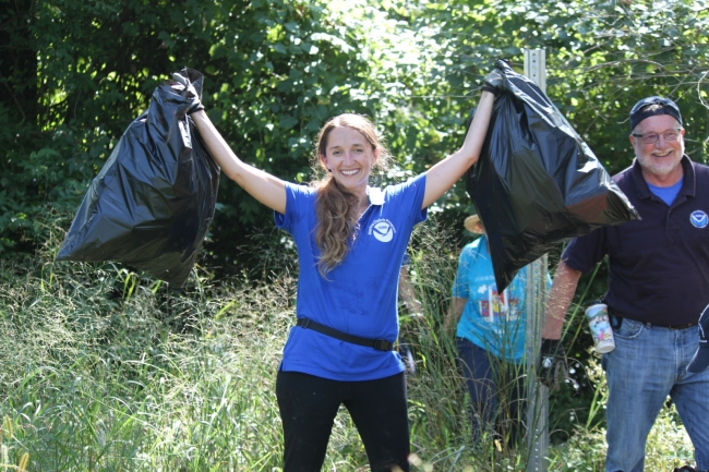 A woman holds up to full garbage bags of collected debris.