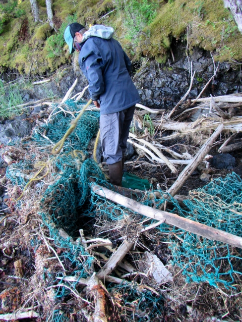 A volunteer standing in net debris.
